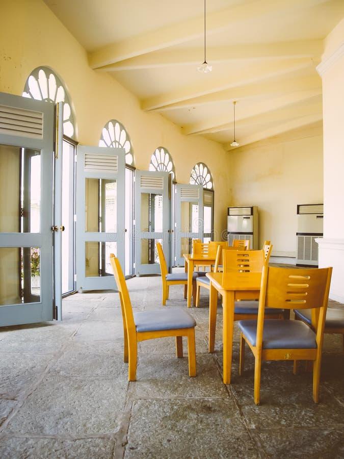 Drewniani krzesła i stół w pokoju z dużym okno - retr fotografia stock