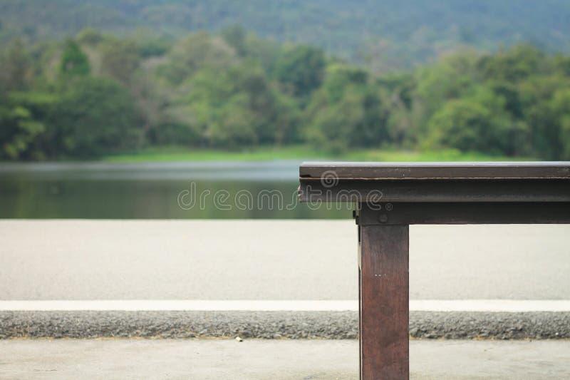 Drewniani krzesła w parku Tam jest tła wizerunek rezerwuar i góra zakrywający drzewo fotografia stock
