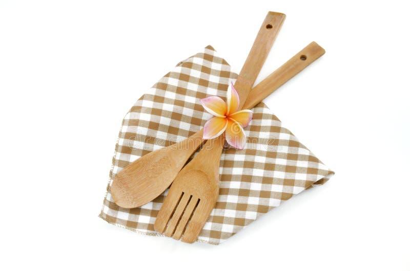 Drewniani kulinarni naczynia i kwiat z brown w kratkę płótnem odizolowywającym na bielu obraz royalty free