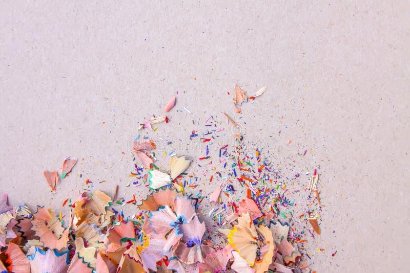 Drewniani ołówkowi golenia i kolorowe kruszki grafit od ostrzarki na miękkich części menchii pastelu tapetują tło Odgórny widok P zdjęcie royalty free