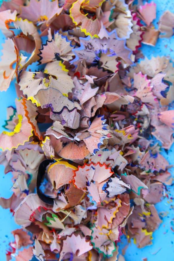 Drewniani ołówkowi golenia i kolorowe kruszki grafit od ostrzarki na miękkim pastelu tapetują tło Odgórny widok Projektów element obrazy stock