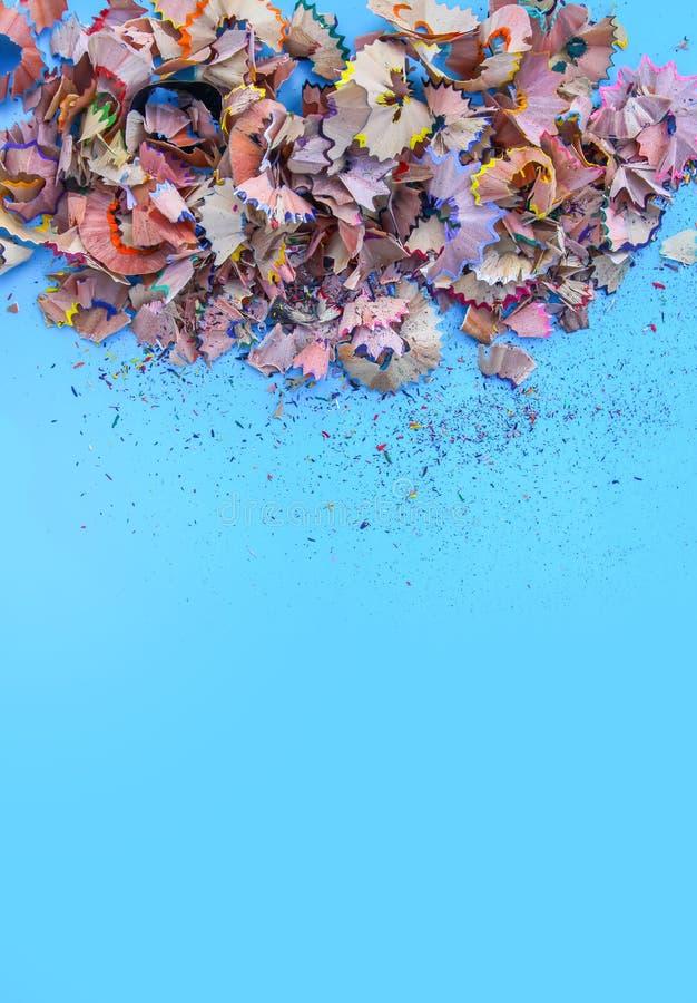 Drewniani ołówkowi golenia i kolorowe kruszki grafit od ostrzarki na miękkim pastelu tapetują tło Odgórny widok Projektów element obraz royalty free