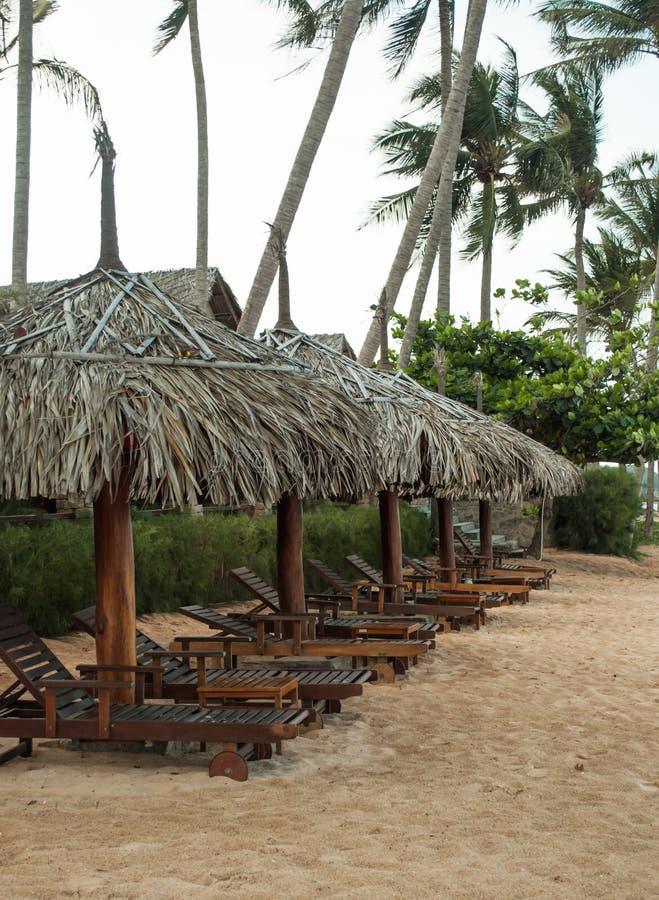 Drewniani sunbeds na monsun plaży obrazy stock