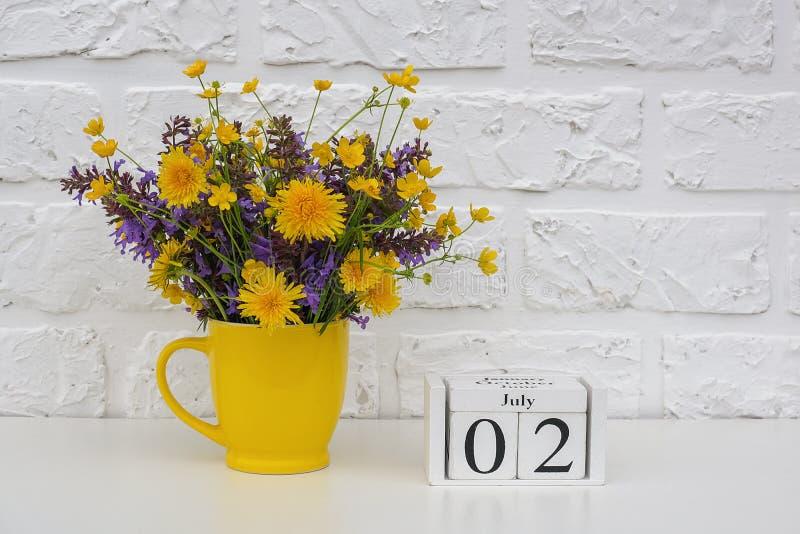 Drewniani sześciany kalendarzowy Lipiec 2 i żółta filiżanka z jaskrawymi barwionymi kwiatami przeciw białej ścianie z cegieł Szab obrazy royalty free