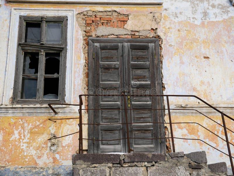 Drewniany, łamający okno, blokujący drzwi na zaniechanym rozdrabnianie cegły domu obrazy stock
