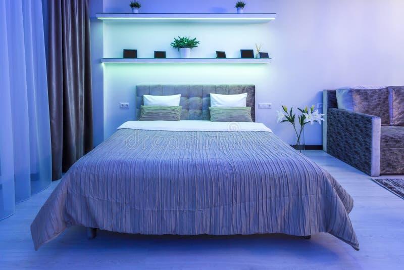 Drewniany łóżko w wnętrzu nowożytna sypialnia w loft mieszkaniu w drogich mieszkaniach w neonowym świetle fotografia stock