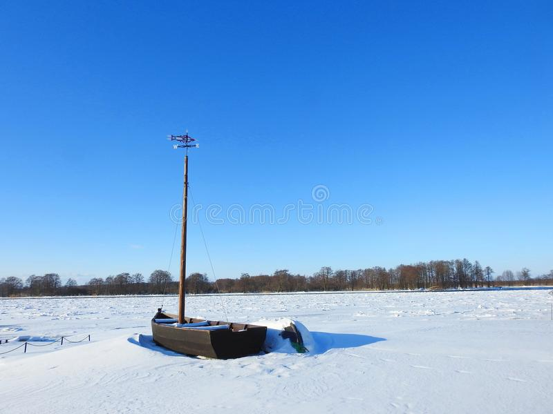 Drewniany żeglowanie statek na brzegowej pobliskiej rzece w zimie, Lithuania obraz stock