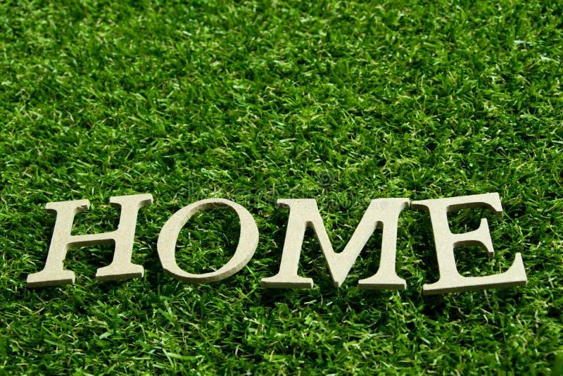 Drewniany abecadło w sformułowaniach stwarza ognisko domowe na sztucznym zielonej trawy backgr zdjęcia stock