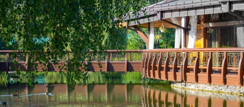 Drewniany alkierz blisko jeziora z kaczkami i drzewami Ogrodowy dom z odbiciem w wodzie zdjęcia stock