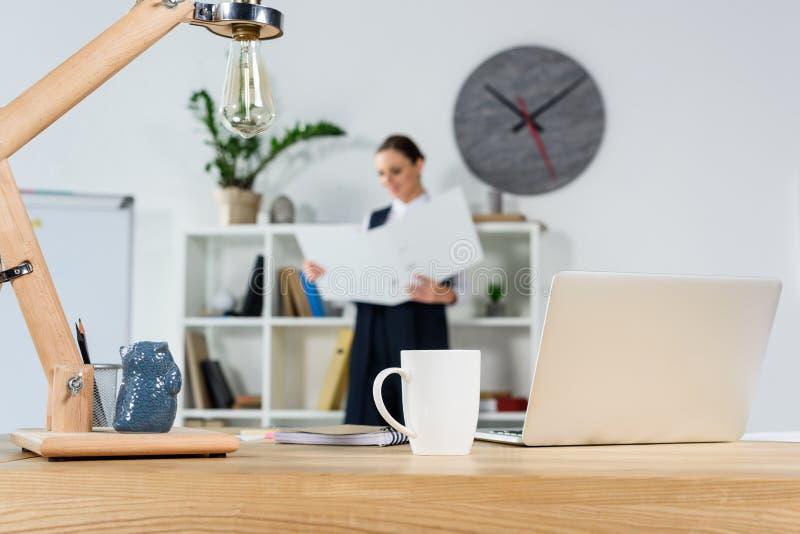 Drewniany biurko w nowożytnym biurze z laptopem, filiżanką kawy i materiały, podczas gdy młody bizneswoman obraz royalty free
