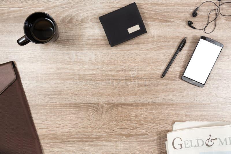 Drewniany biurko z smartphone, hełmofony, pióro, portfel, kawowy kubek zdjęcie stock