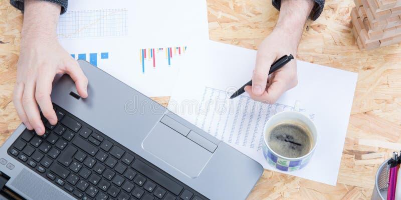Drewniany biurowego biurka stół z laptopem, ręki kobietą, filiżanką i dostawami, Odg?rny widok z kopii przestrzeni?, mieszkanie n zdjęcia royalty free