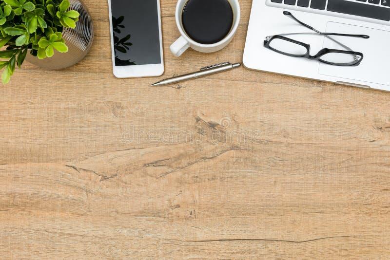 Drewniany biurowego biurka stół z laptopem, smartphone, filiżanką kawy i dostawami, zdjęcia royalty free