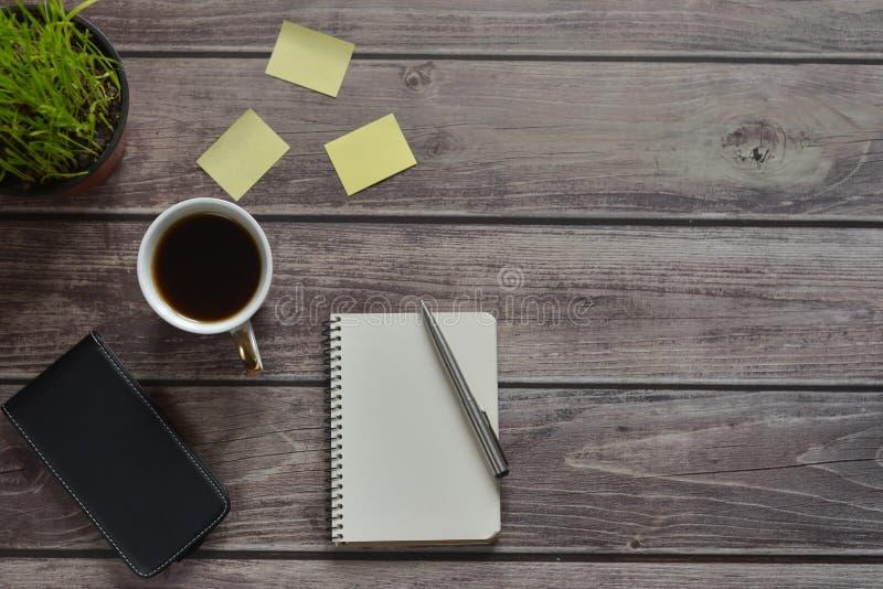 Drewniany biurowego biurka stół z notatnikiem, rękojeścią, telefonem, filiżanka kawy i kwiatu garnkiem, zdjęcie royalty free