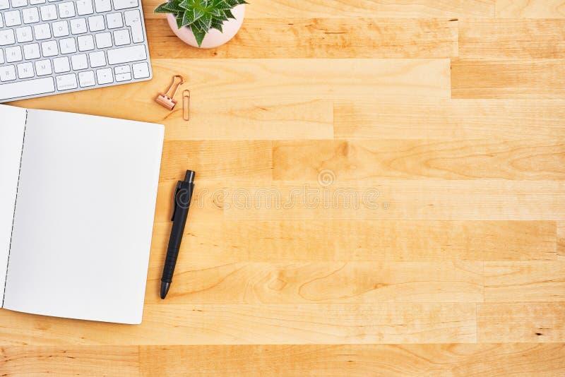 Drewniany biurowego biurka stół z pustym notatnikiem, piórem i komputerem, obrazy stock