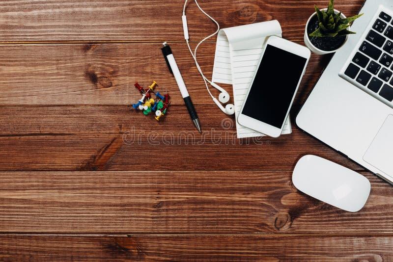 Drewniany biurowego biurka st?? z laptopem, fili?anka kawy i dostawami, obraz stock