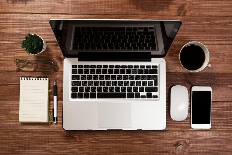 Drewniany biurowego biurka st?? z laptopem, fili?anka kawy i dostawami, obraz royalty free