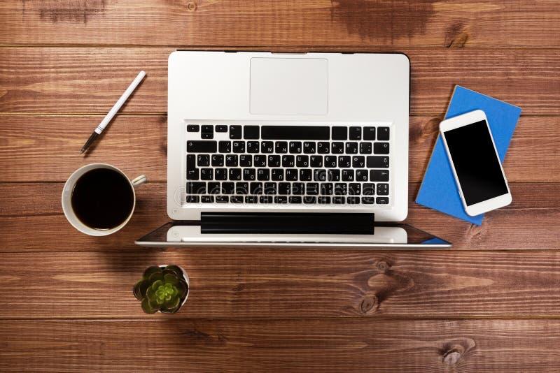 Drewniany biurowego biurka st?? z laptopem, fili?anka kawy i dostawami, zdjęcia royalty free
