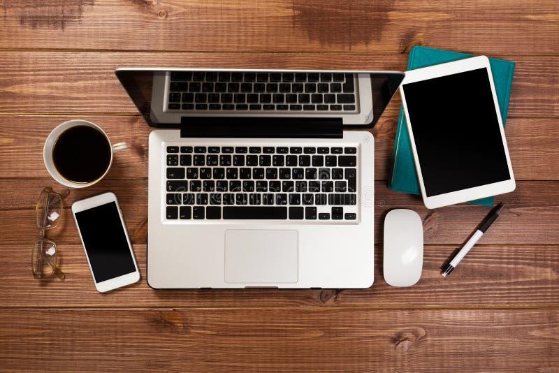 Drewniany biurowego biurka st?? z laptopem, fili?anka kawy i dostawami, zdjęcia stock
