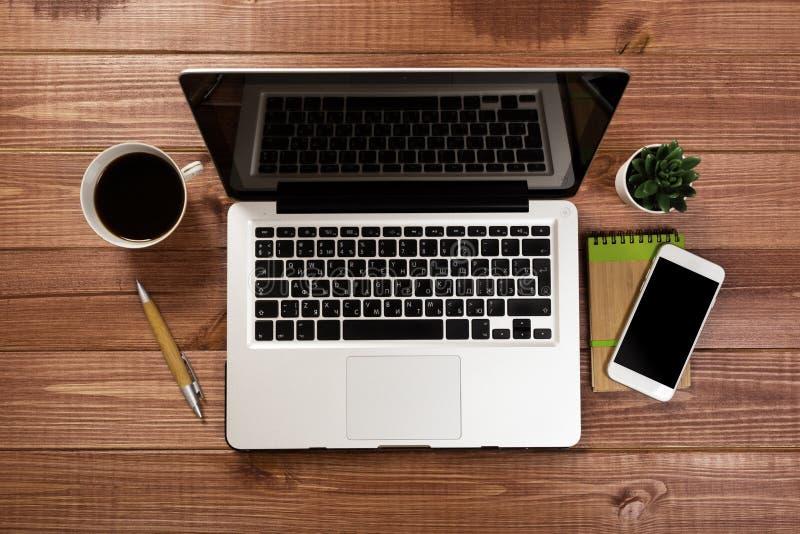 Drewniany biurowego biurka st?? z laptopem, fili?anka kawy i dostawami, obrazy stock