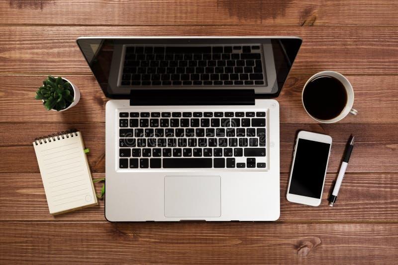 Drewniany biurowego biurka st?? z laptopem, fili?anka kawy i dostawami, fotografia royalty free