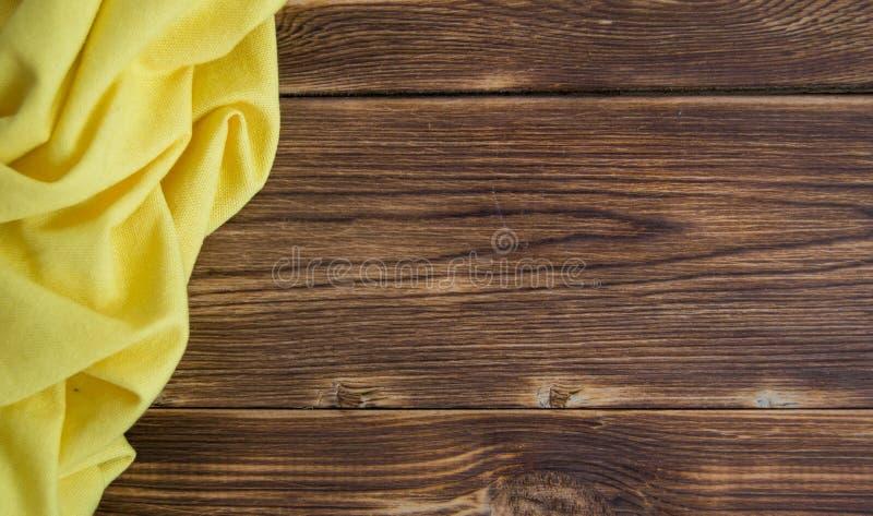 Drewniany brązu stół z nowym pielucha kolorem żółtym zdjęcie royalty free