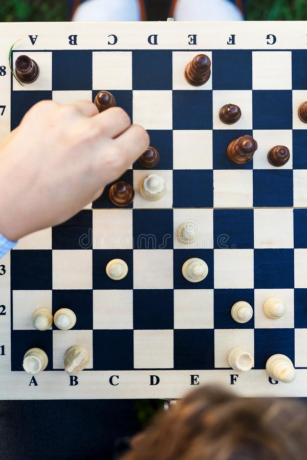 Drewniany chessboard z postaciami na nim ręka robi ruchowi Odgórny widok, zamyka up Intelektualna gra obrazy stock
