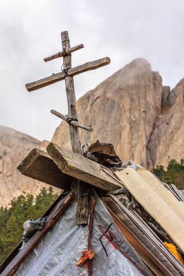 Drewniany chrześcijanina krzyż na dachu turystyczna buda jako symbol ochrona na skalistym halnego szczytu tle przy wsią Kaukaz, obrazy stock