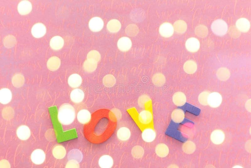 Drewniany colotful list miłosny na różowy prezent zawijającym papierze jako tło z kopii przestrzenią fotografia stock