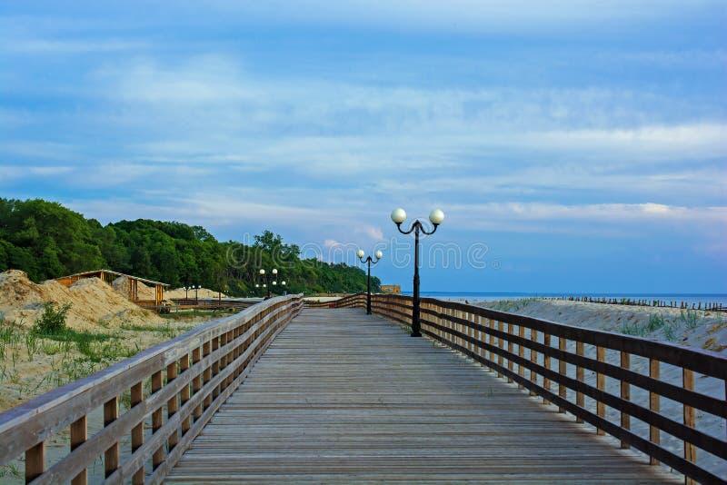 Drewniany deptak na plaży z lampposts przy zmierzchem na Bałtyckim zdjęcie stock