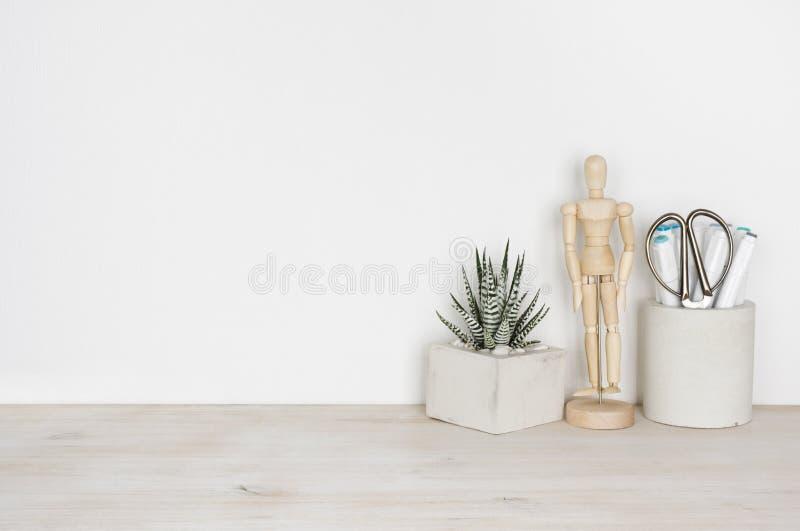 Drewniany desktop z kwiatu garnkiem, ludzkim posążkiem i biurowymi dostawami, fotografia royalty free