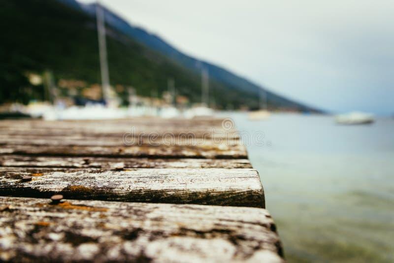 Drewniany doku molo przedłużyć nad błękitną jezioro wodą górami i, rozmyty tło obraz stock