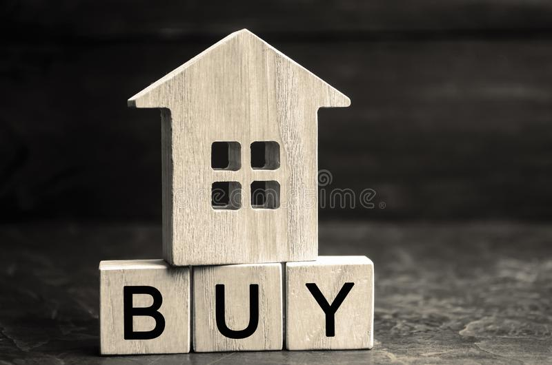 Drewniany dom i «zakup «wpisowy na drewnianych blokach Pojęcie kupienie własność Nabywa dom, mieszkanie, nieruchomość zdjęcie stock