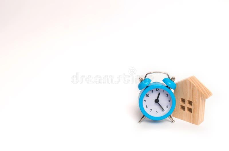 Drewniany dom i błękitny budzik na białym tle Cogodzinny i Chwilowy niedrogi acco zdjęcia royalty free
