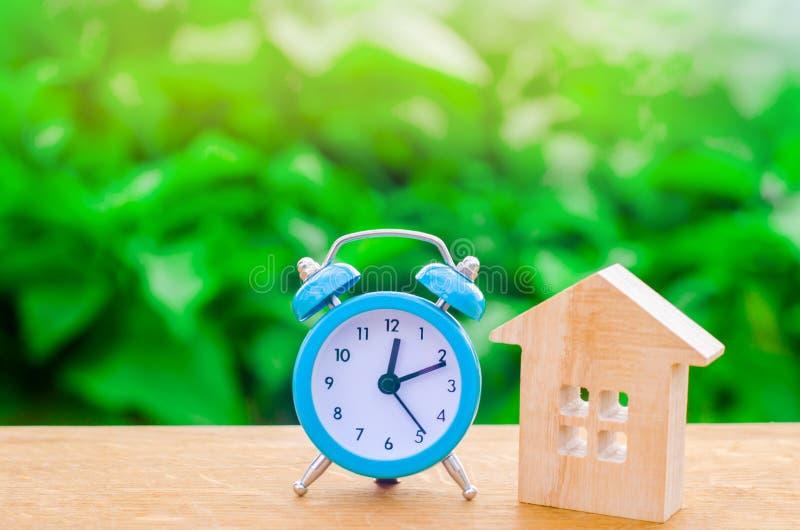 Drewniany dom i błękitny budzik na zielonym tle Cogodzinny i Chwilowy niedrogi acco fotografia stock