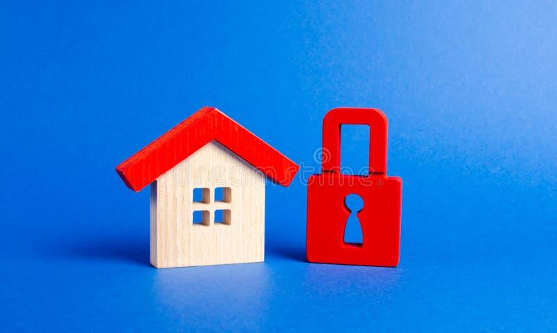 Drewniany dom i czerwona kłódka Niedostępna i droga nieruchomość r?ki mie?c? ubezpieczenie nad ma?ym biel ochrona i bezpiecze?stw zdjęcia royalty free