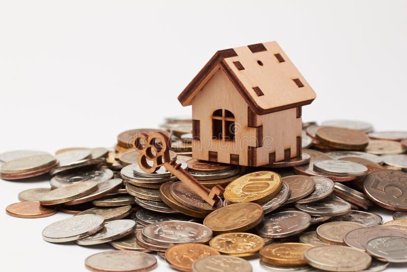 Drewniany dom i klucz na monetach obrazy royalty free