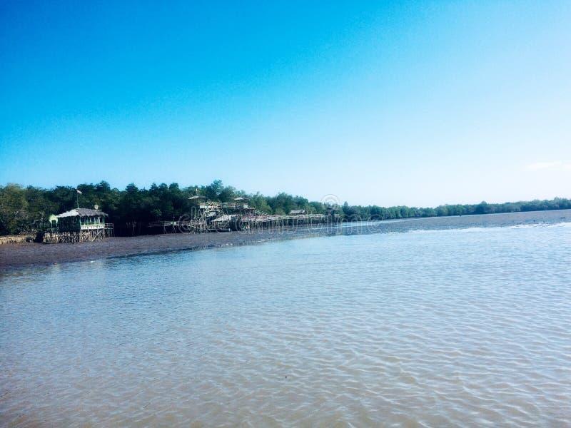 Drewniany dom na dennym przodzie z błękitne wody i niebieskim niebem zdjęcie royalty free