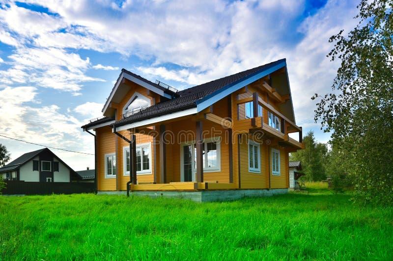 Drewniany dom na zielonej trawie z niebieskim niebem obrazy stock
