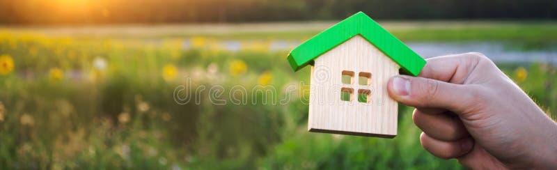 Drewniany dom w rękach w zmierzchu tle koncepcja real nieruchomo?ci Eco ?yczliwy dom Symbol szczęśliwy życie rodzinne fotografia stock
