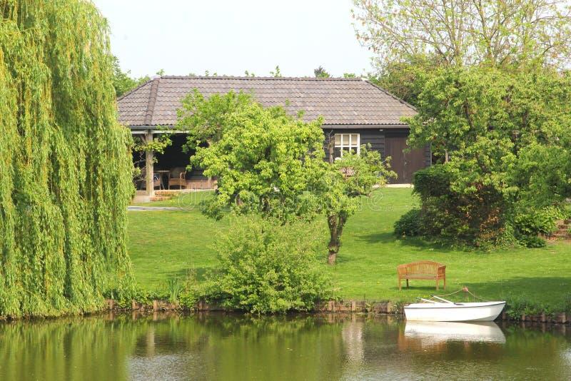 Drewniany dom z ogródem wzdłuż kanału i łodzi, NL fotografia royalty free