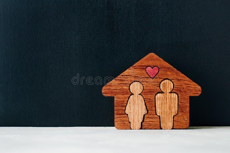 Drewniany dom z postaciami mężczyzna i kobieta na kredowej deski backgr zdjęcie royalty free
