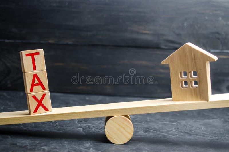 Drewniany dom z wpisowym «podatkiem jest na skalach Podatki na nieruchomości, zapłata Kara, zaległości Rejestr podatnicy obrazy royalty free
