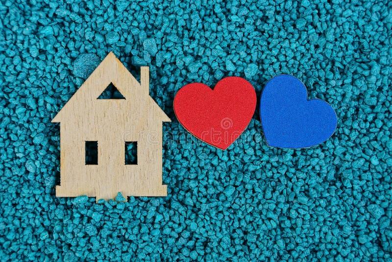 Drewniany domowy układ i dwa barwiliśmy serca na błękitnym piasku zdjęcie stock