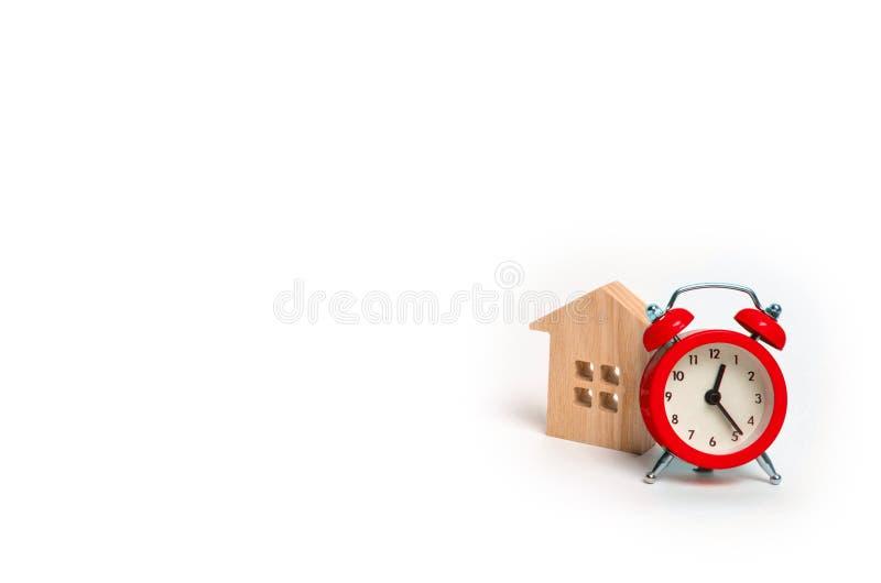 Drewniany domu i czerwieni budzik na białym tle Cogodzinny i Chwilowy niedrogi accom fotografia stock