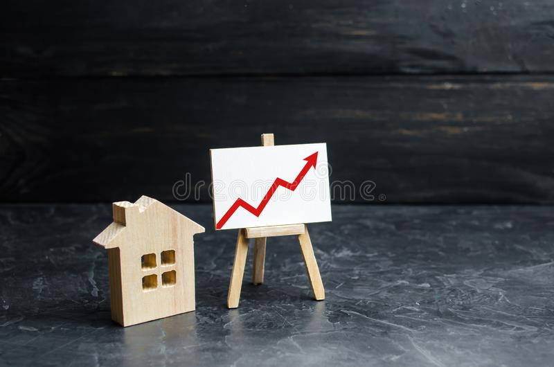 Drewniany domu stojak z czerwoną strzałą w górę Rosnący popyt dla mieścić i nieruchomości Przyrost miasto i swój populacja Inv zdjęcia royalty free