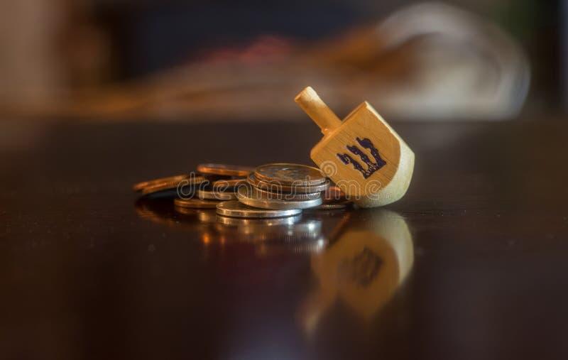 Drewniany Dreidel Odpoczywa na stosie monety obrazy royalty free