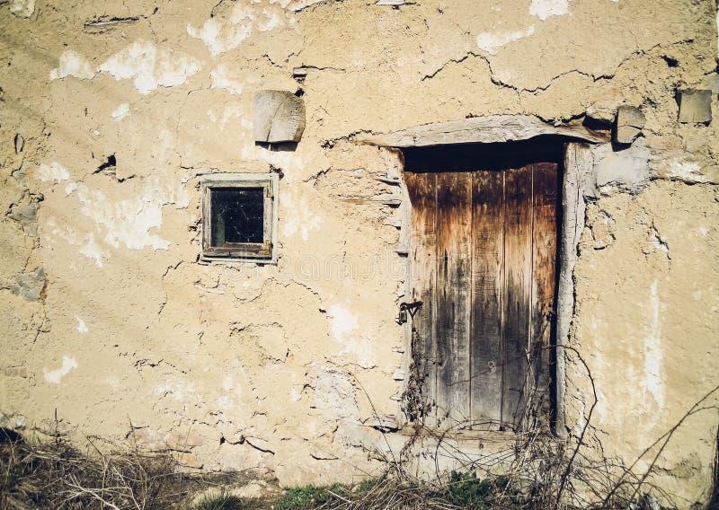 Drewniany drzwi i okno na starym zaniechanym domu glina w zaniechanej Serbskiej wiosce zdjęcie royalty free