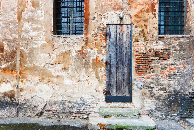 Drewniany drzwi w podławym ściana z cegieł obrazy royalty free