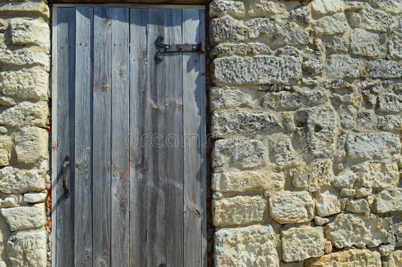 Drewniany drzwi z metali zawiasami instaluje w ścianie antyczny kamień zdjęcie stock